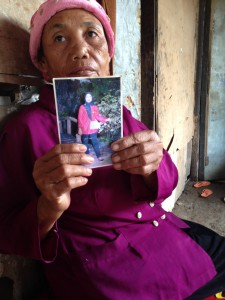 Darasih holds up a photo of her daughter Kartini who works in Saudi Arabia. She has neither heard nor received money from her in the last couple of years., whom she has lost touch with
