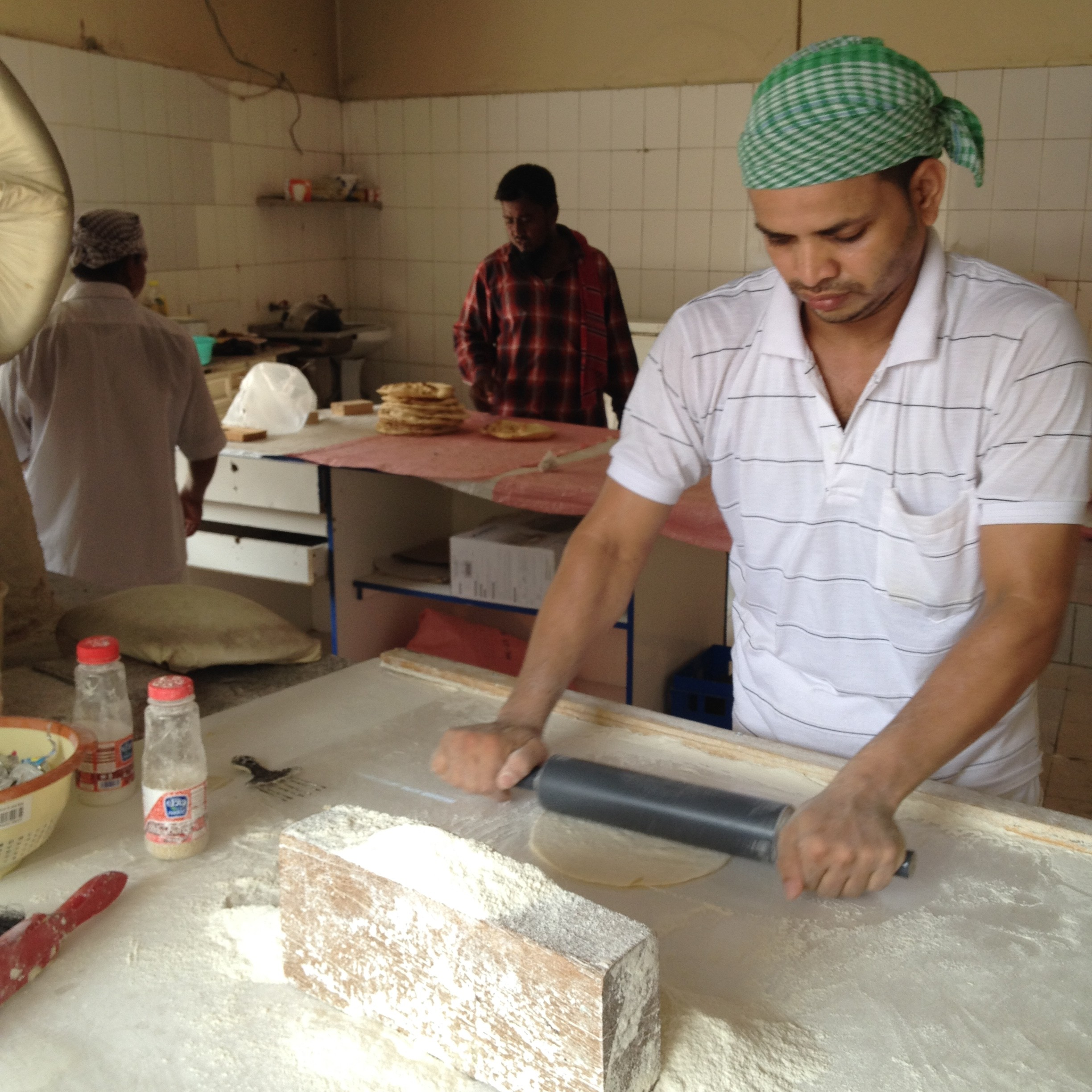 Migrant workers operate the local bakeries in Bahrain. In the Gulf region, these bakeries offer their fresh bread at cheap rates than the packaged bread sold in supermarkets. Bakers endure working around high temperature stone chambers all day, taking breaks from work only for prayers.