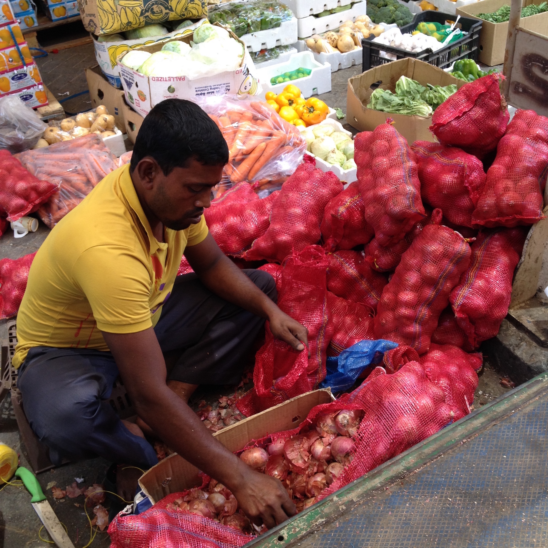 This vendor is cleaning sacks of onions to have them ready for sale.